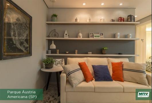 Sala de estar com sofá neutro e almofadas coloridas para quebrar a monotonia do ambiente
