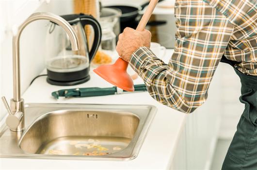 Profissional da limpeza realizando trabalho de desentupimento de uma pia em apartamento