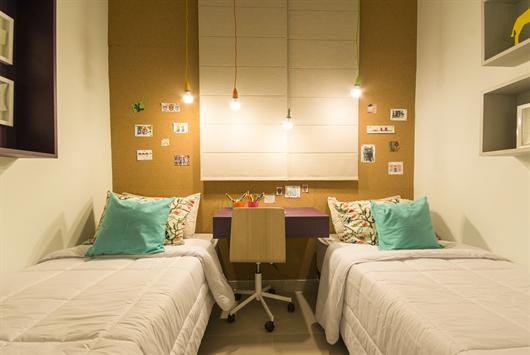 Quarto infantil decorado com mesinha de estudos, duas camas e luminárias pendentes
