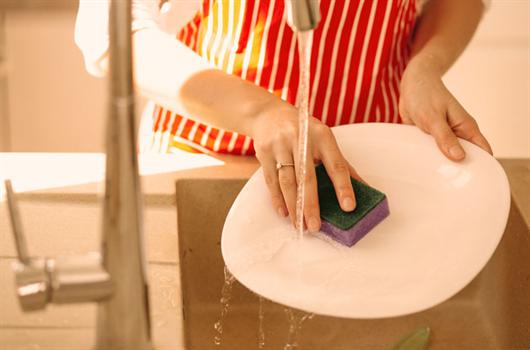 Exemplo de desperdício de água: mulher lavando louça com a torneira aberta