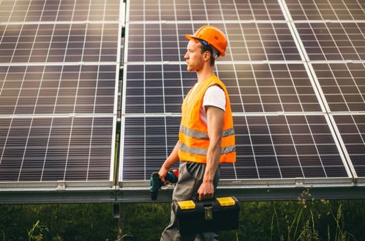 Engenheiro inspecionando e dando manutenção nas placas de energia solar fotovoltaicas