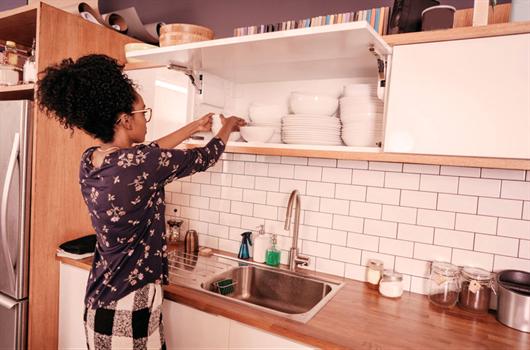 Dona de casa organizando as vasilhas no armário da cozinha
