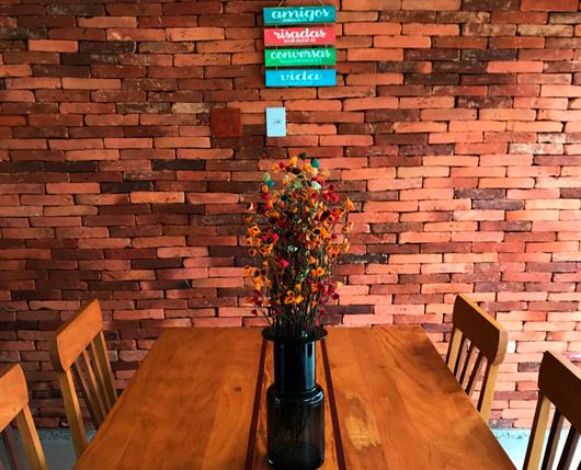 Espaço decorado com papel de parede que imita tijolinho de barro