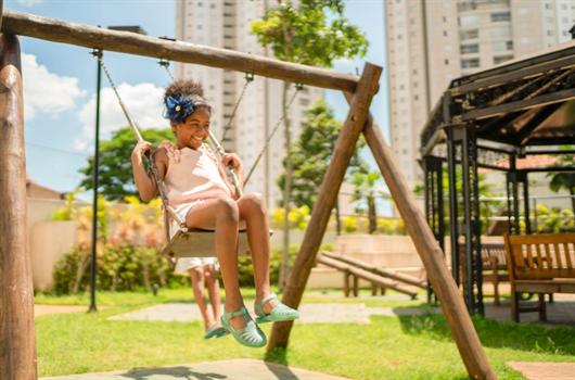 Menina aproveitando seu momento de descanso para brincar na área de lazer de seu condomínio