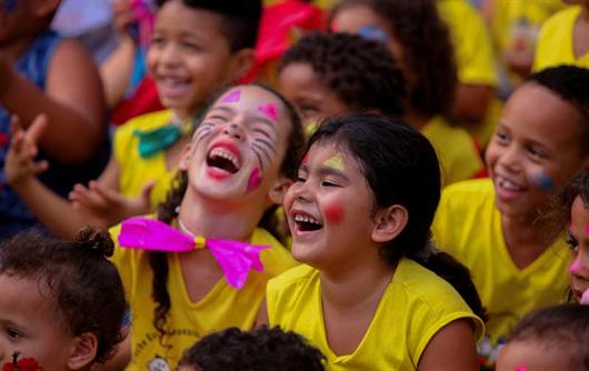 Crianças felizes aproveitando o tempo livre para brincar e se divertir com apoio de projetos sociais
