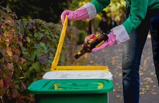 Mulher descartando o lixo de maneira segura usando luvas para não se contaminar com o Coronavírus