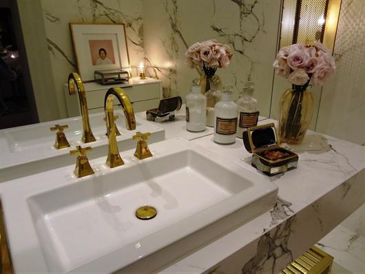 Pia de banheiro decorada com porta joias, cremes e flores