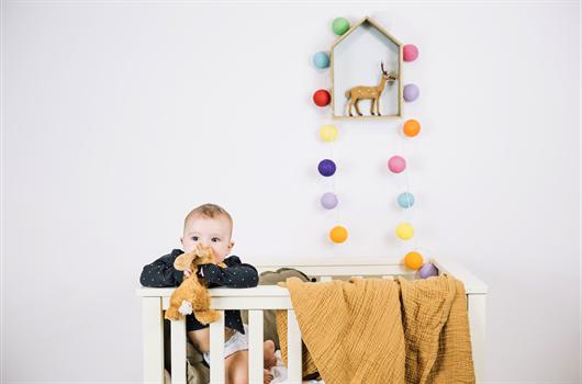 Quarto de recém-nascido decorado com mobile e pompons coloridos