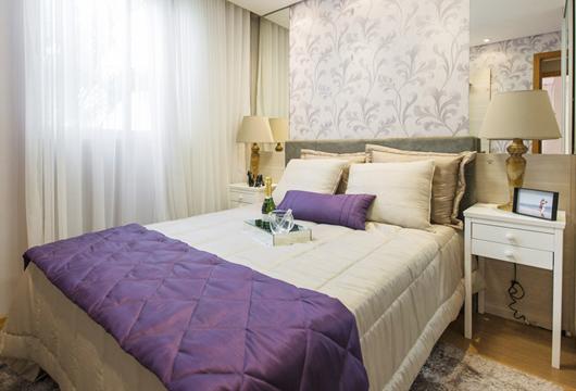 Quarto decorado com cama de casal com composição de mantas