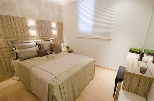 Cama de casal com cabeceira em tons neutros acompanhando a decoração do quarto