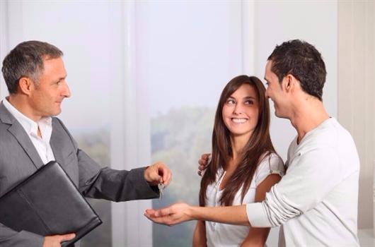 Casal recebendo a chave do apartamento recém comprado
