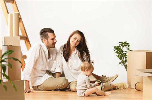Quarto de bebê com dois berços, uma poltrona de amamentação e nichos decorativos
