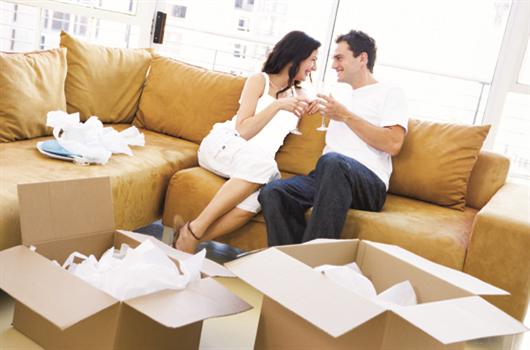 Casal sentado na sala do apartamento novo que acabaram de se mudar