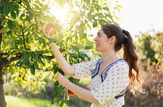 Mulher feliz pela conquista de seu apartamento MRV com uma área verde com pomar