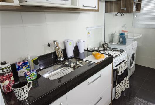 Pia da cozinha de apartamento organizada de forma funcional