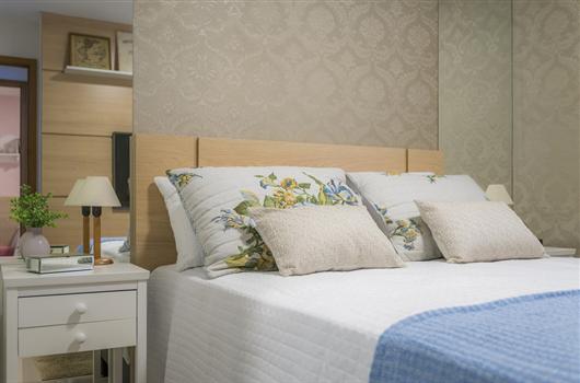 Decoração de cama com colcha azul e detalhes em branco e floral