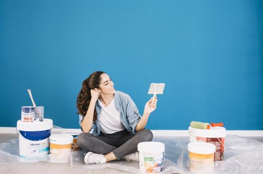 Mulher pintando a parede de seu apartamento para aderir às tendências de decoração