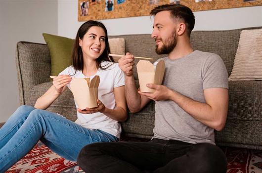 Casal em seu apartamento pedindo comida através de serviços de Delivery