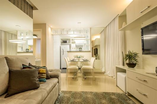Sala de estar decorada com espelhos atrás do sofá para ampliar o ambiente