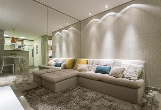 Sala de estar decorada com tapete, sofá e papel de parede neutros e almofadas coloridas