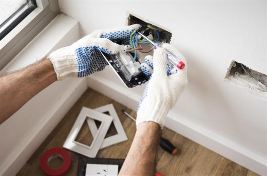 Homem realizando a instalação elétrica em um apartamento