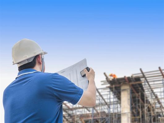 Engenheiro em canteiro de obra orientando outros trabalhadores da construção civil