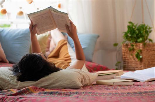 Mulher lendo seus livros em cima da cama