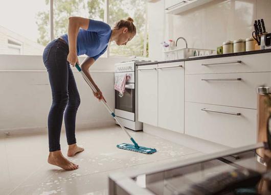 Mulher limpando o chão com produtos de limpeza