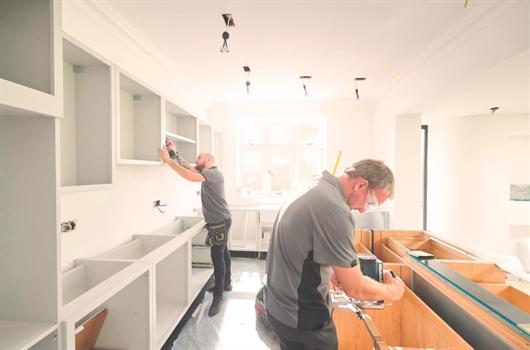 móveis planejados sendo instalados na cozinha de um apartamento
