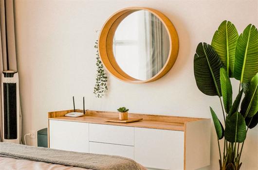 Móvel espelhado na parede onde o próprio espelho funciona como objeto de decoração