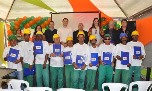 Operários de obras da MRV segurando o diploma de alfabetização