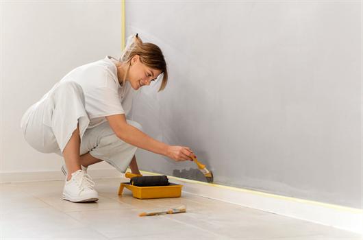 Mulher pintando a parede com cinza claro