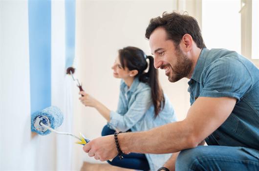 Casal pintando as paredes de seu apartamento pela primeira vez