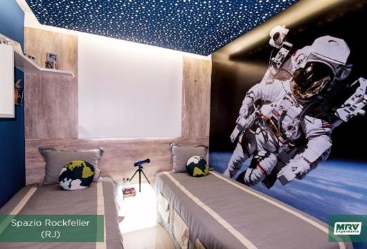 Quarto de adolescente com tema espacial nas paredes e criado mudo iluminado